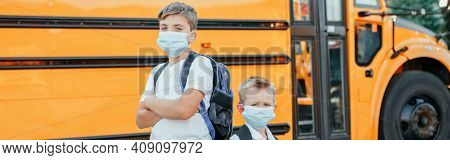Brothers Students Kids Wearing Face Mask Near Yellow Bus. Education And Back To School In September.