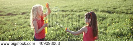 Catch A Bubble. Girls Friends Blowing Soap Bubbles In Park On Summer Day. Kids Having Fun Outdoor. A