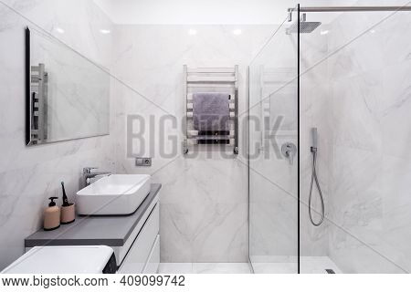 Bathroom Interior Concept. Shower Cabin With Glass Wall Near Clean Fresh Towel On Heated Rail At Cer