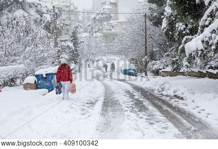 A Woman Goes Home Loaded With Bags From The Supermarket Along A Snowy Street In Athens, Greece, 16th