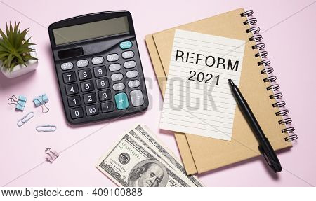 The Text Reform 2021 On Office Desk With Calculator, Markers, Glasses And Financial Charts.