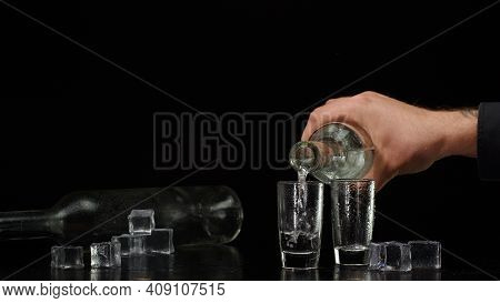 Bartender Pouring Up Frozen Vodka From Bottle Into Two Shots Glasses With Ice Cubes Isolated On Blac