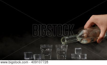 Bartender Pouring Up Two Shots Of Vodka With Ice Cubes From A Bottle Into Glasses Against Black Back