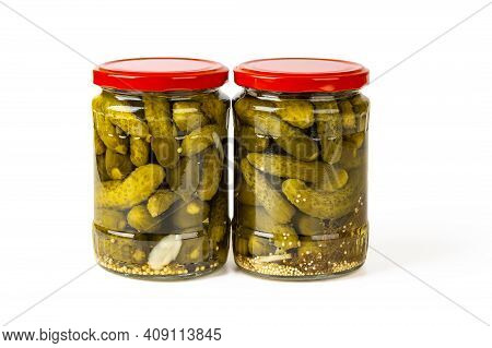 Two Full Glass Jars Of Pickled Gherkins Isolated On A White Background. Whole Green Cornichons Marin