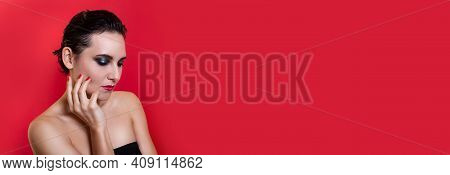 Horizontal Banner. Woman With Bright Makeup And Pensive Face Posing On Red Studio Background. Copy S