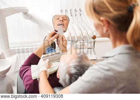 Dentist And Patient Choosing Shade Of Tooth Enamel