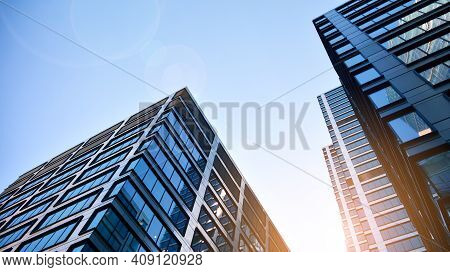 Bottom View Of Modern Skyscrapers In Business District Against Blue Sky. Looking Up At Business Buil