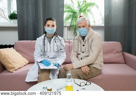 Sick elderly patient and young general practitioner in protective masks sitting on couch next to one another in front of camera in living-room