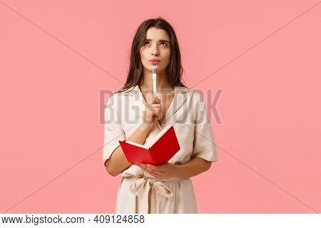 Thoughtful And Creative Young Woman Making List, Pouting And Looking Up Pensive And Inspired, Holdin
