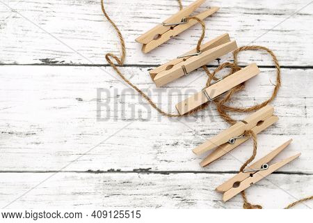 Wooden Clothespins With Hemp String On White Wooden Table