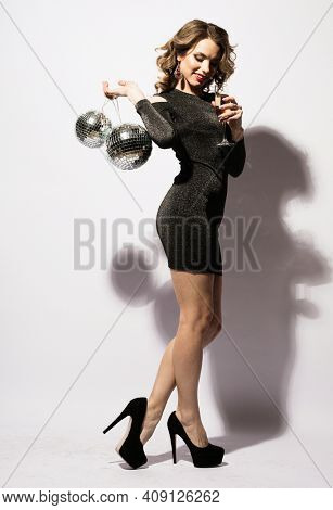 Christmas, celebration party, holiday concept. Young woman in evening dress holding champagne and disco ball. Brighrt make up and Wavy hairstyle.