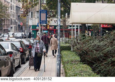 Belgrade, Serbia - October 24, 2020: Old Senior Woman Wearing A Respiratory Face Mask Walking With H