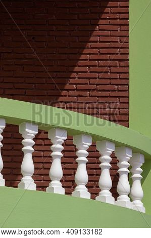 White And Green Curved Balustrade On Terrace With Sunlight And Shadow On Brick Wall Surface In Vinta