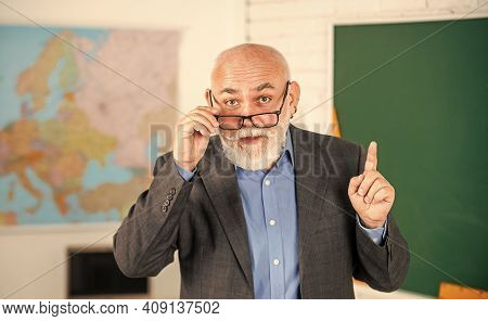 Answer And Question. Senior Man Teacher At Blackboard. Bearded Tutor In Glasses Near Geography Map.