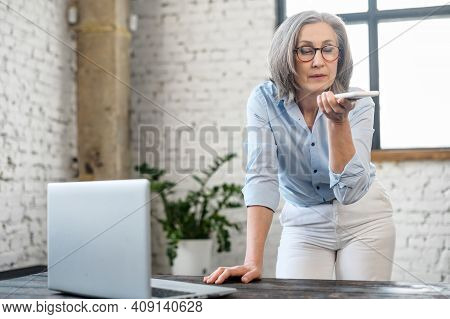 Busy Successful Multitasking Senior Elder Businesswoman Standing By The Office Desk, Talking To A Cl