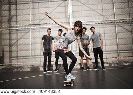 Young Asian Woman Skateboarder Skateboarding Outdoors With Friends Watching From Behind