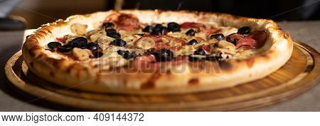 American Pizza With Olives On A Round Board On A Table In A Pizzeria. Banner For Pizzeria And Bakery