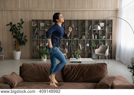 Happy Indian Female Renter Dancing On Sofa At Home