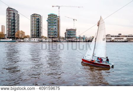 London, Uk - April 17 2014: A Sailboat On The River Thames. Nine Elms Is In The Background With Resi