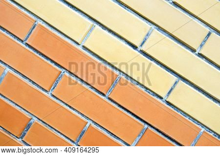 Wall Of Two Colors Of Brickwork, Natural Texture, Surface. Yellow And Orange Bricks Are Located Diag