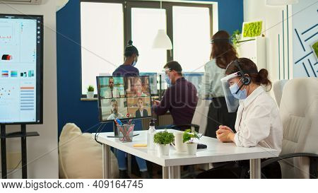 Manager With Protection Mask And Visor Having Videomeeting Discussing Online Using Headset With Remo