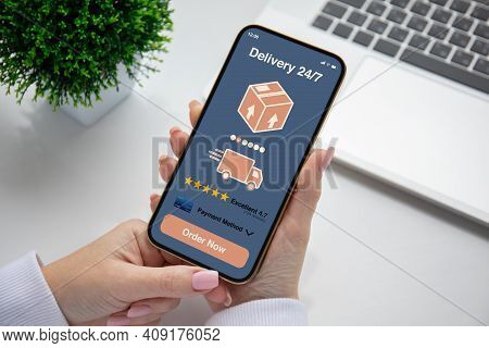Female Hands Hold Phone With Parcel Delivery Application On Screen Background Table In Office