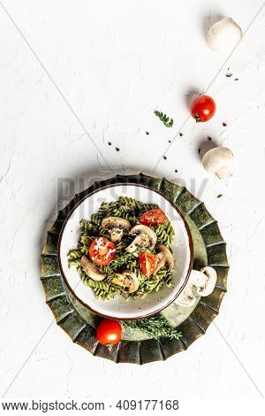 Vegetarian Vegetable Green Pasta Spinach Leaves And Cherry Tomatoes On Liht Background. Pasta Vegan