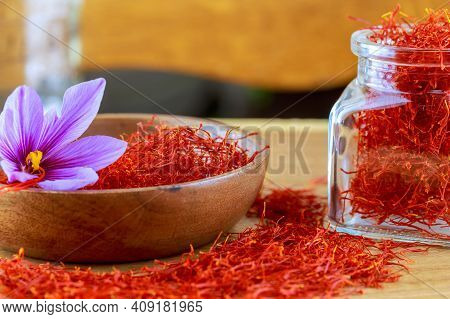 Dry Saffron Stigmas And A Single Crocus Flower In A Wooden Plate On A Wooden Surface. Saffron .