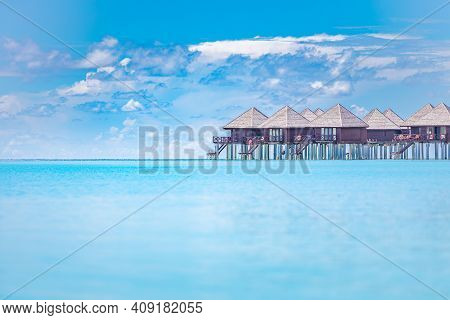 Overwater Bungalow In The Indian Ocean. Row Of Bungalows In Clean Water And Azure Sky With Clouds, E