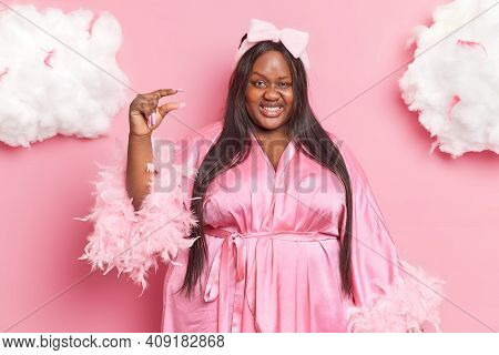 Cheerful Plus Size Lady With Dark Skin Shapes Tiny Or Little Object Demonstrates Small Size Smiles G