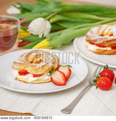 Profiteroles Or Cream Puff Cakes With Whipped Cream And Strawberries, Served On Table With Tulip Flo