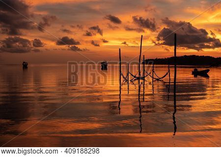 Perfect Cambodian Sunrise With Calm Waters Colorful Reflection And Ocean Hammocks In The Foreground