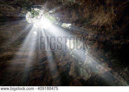 Upward Shot Of Light Rays Entering A Deep Cave And Illuminating The Surrounding Stone Walls