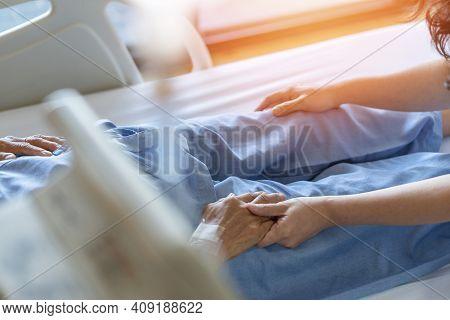 Caregiver And Elderly Senior Patient (aged Old Adult Person) Holding Hands In Hospital Bed Or Nursin