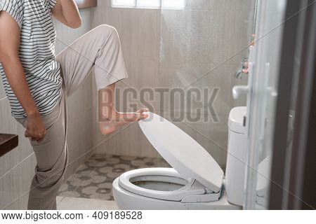 Close Up Of A Womans Feet Closing The Smelly Toilet Lid