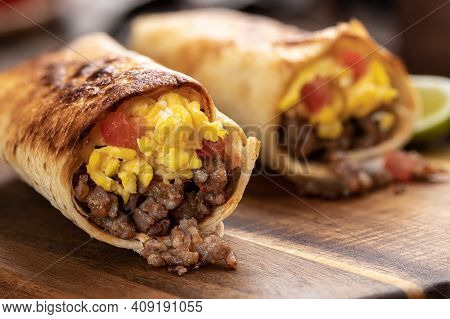 Closeup Of Two Breakfast Burritos With Scrambled Egg, Sausage And Tomato In A Tortilla Wrap