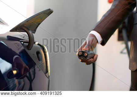 Electric Vehicle Charging Station. Charger For Ev Car. African American Mans Hand Holding Ev Car Cha