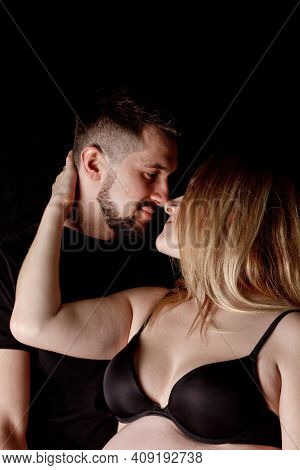 A Man And A Pregnant Woman Couple In Their Ninth Month Of Pregnancy Are Embracing Against An Isolate