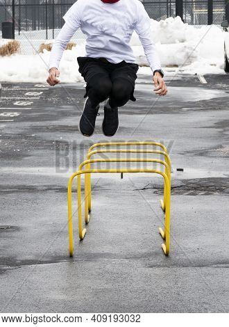 Front View Of A High School Track Runner Jumping Over Yellow Hurdles In A Parking Lot During Practic