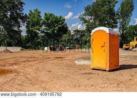 Porta Potty On An Active Construction Site With Earth Moving Equipment In The Background