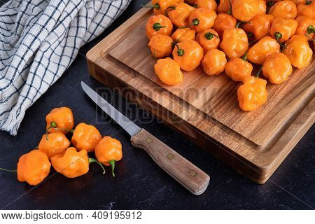 Photograph Of Freshly Picked Habanero Peppers On A Wood Cutting Board With A Knife And Dish Towel On