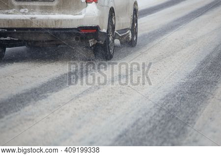 Road Snow Pieces Flow From Wheels Of Dirty White Car Moving Fast In Daylight City With Selective Foc