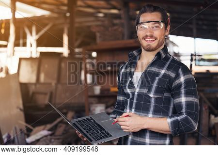 Young Woodworker With Beard Leaning Over Workbench In His Large Workshop Full Of Carpentry Equipment