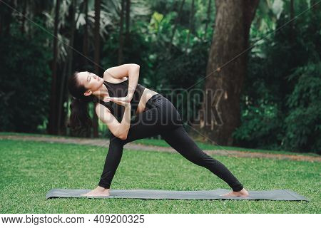 Asian Woman Practicing Yoga In Prep Poses For Side Crane Pose For Parsva Bakasana On The Mat In Outd
