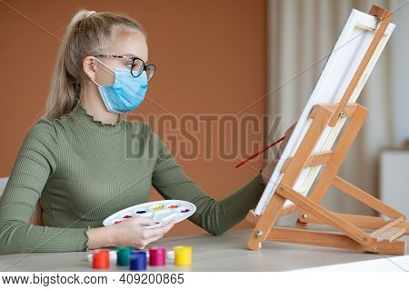 School Girl In Protective Face Mask With Palette And Brush Drawing On Easel, Side View, Copy Space.