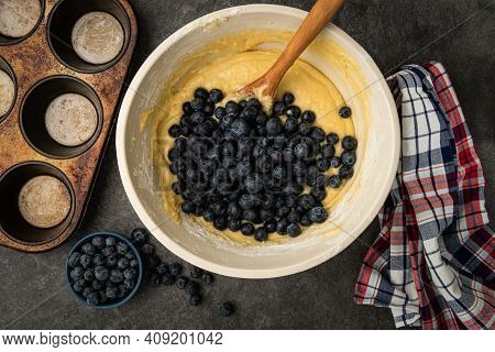 Blueberries Being Added To The Batter To Make Blueberry Muffins