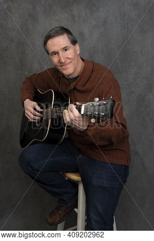 Man Sitting On Stool Picking Acoustic Guitar Smiling At Camera