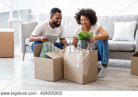 Young African Couple Moving House Packing Belongings In Cardboard Boxes Preparing For Relocation At