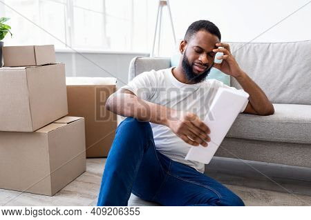 Apartment Renting Cost. Frustrated African Man Reading Paper Or Expenses Bill Sitting Among Packed M