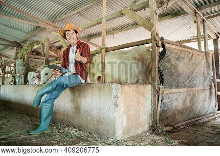 Handsome Rancher Wearing A Cowboy Hat Poses Sitting With One Thumbs Up While Using A Digital Tablet